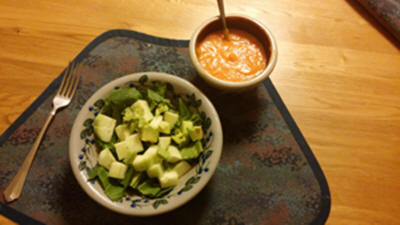 A picture of a salad and soup on a table ready to eat